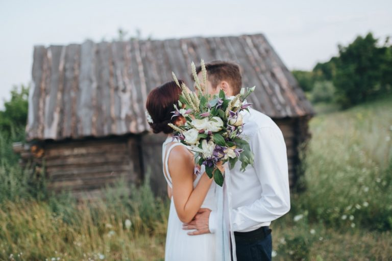 newly weds kissing in front of a wooden house