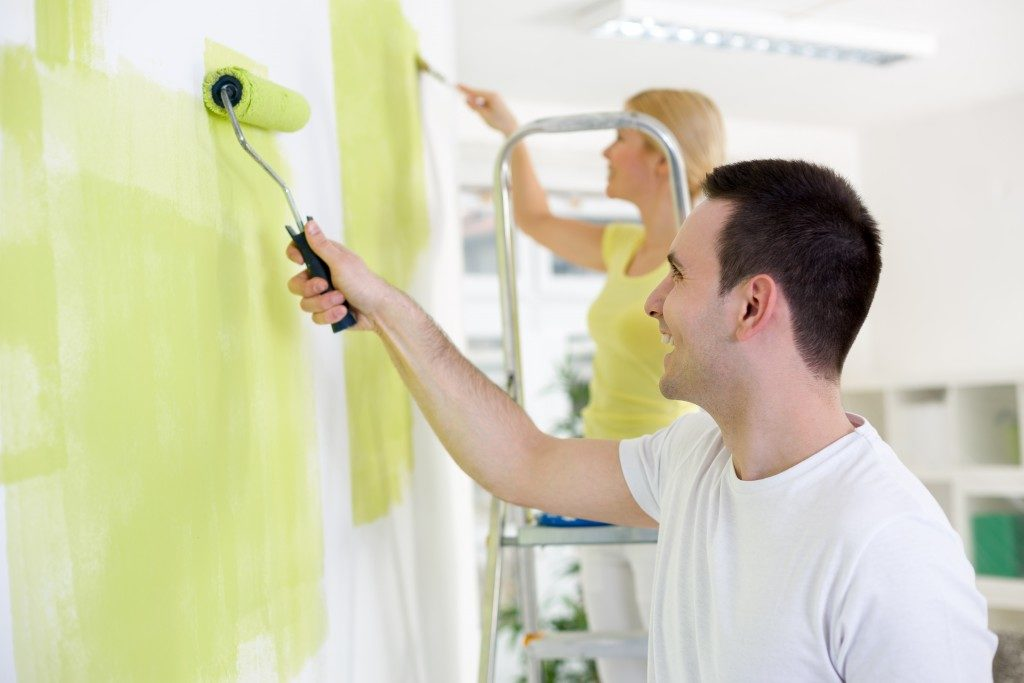 Smiling young couple painting home