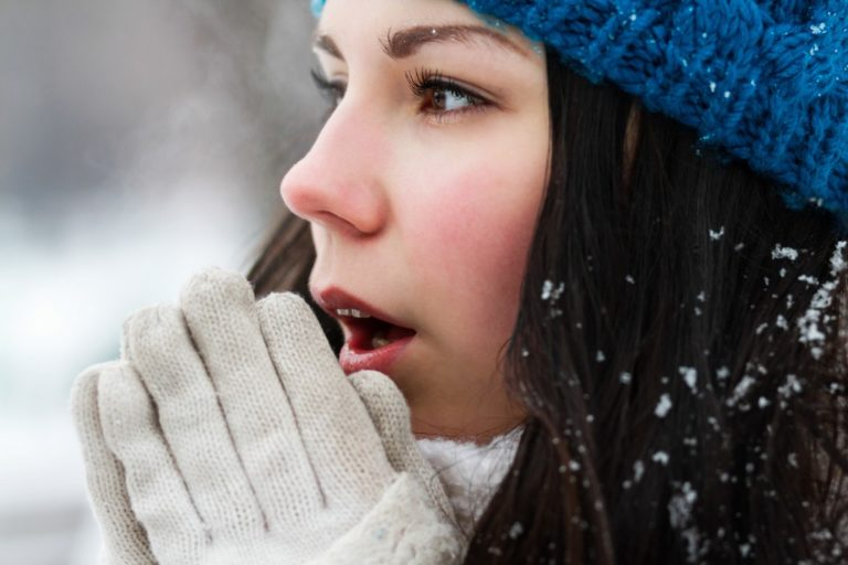 Girl trying to warm her hands during winter