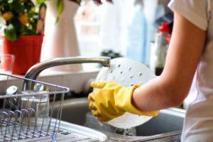 person washing dishes wearing gloves