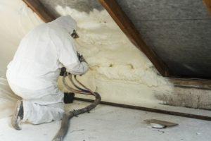 Man placing wool in attic