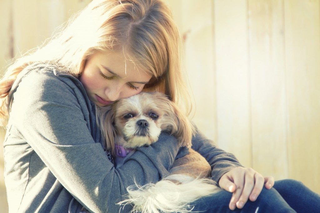 Sad girl hugging a dog
