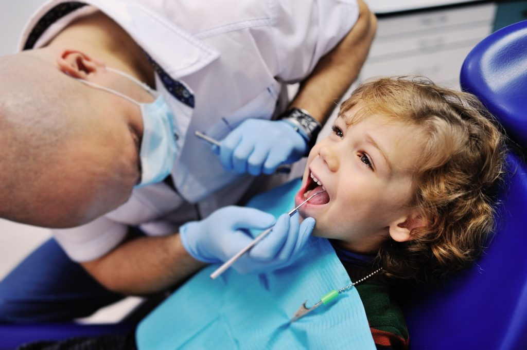 child's teeth being checked by a dentist