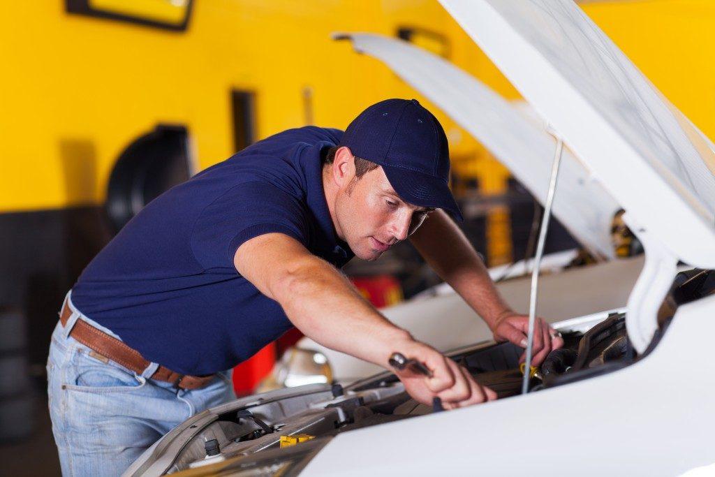 Auto mechanic repairing vehicle inside workshop