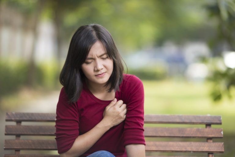 woman sitting on a bench outside experiencing pain in the chest