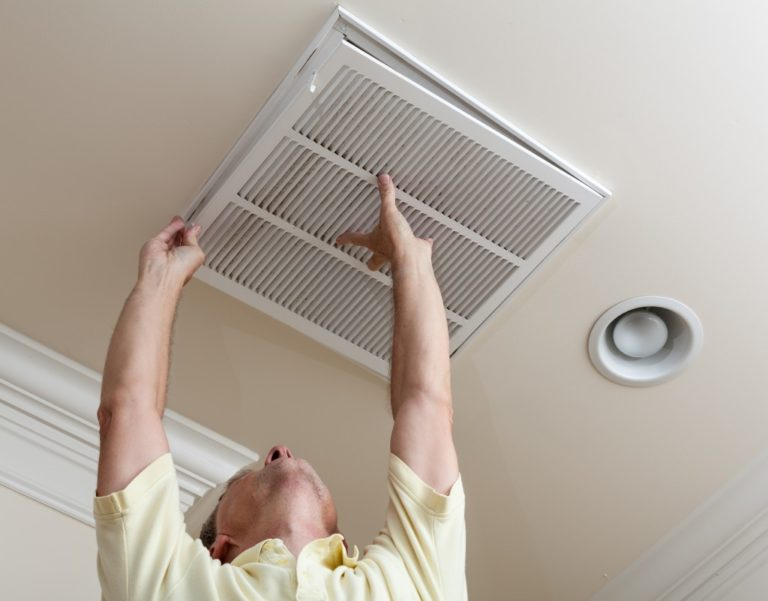 Man installing an air filter on the ceiling