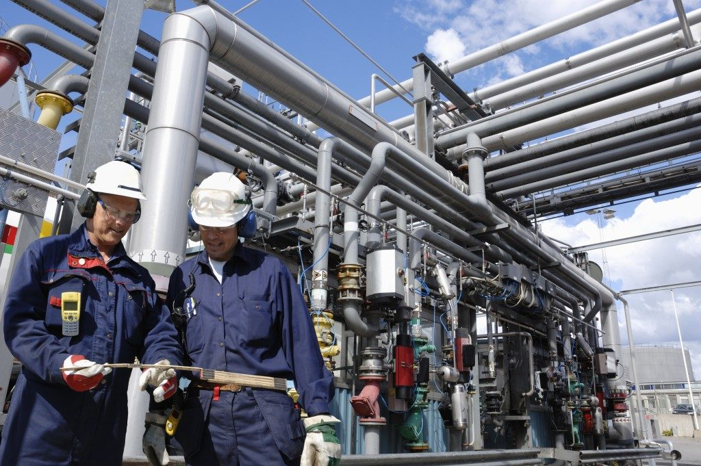 pipes and men working in an oil and gas plant