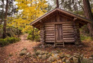Log cabin in a forest in the fall