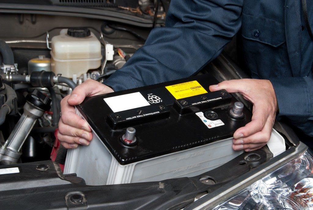 A car mechanic replaces a battery