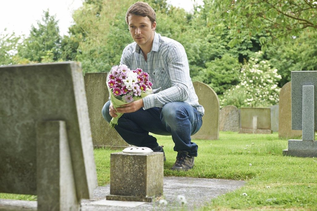 man holding flowers in front of a headstone