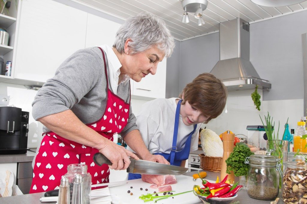Grandmother teaching young boy to cook meat