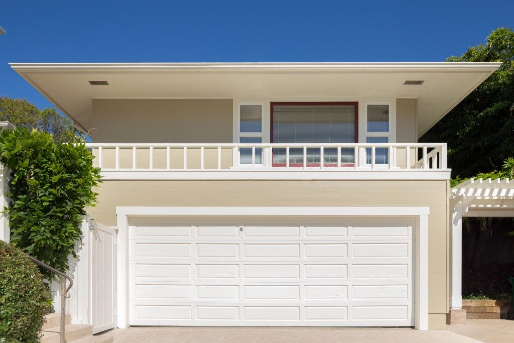 Double white painted garage doors exterior in flat roof house