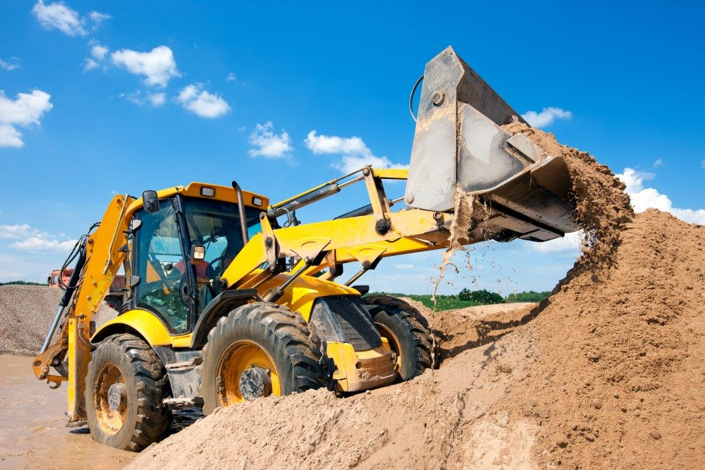 Excavator unloading soil in construction site