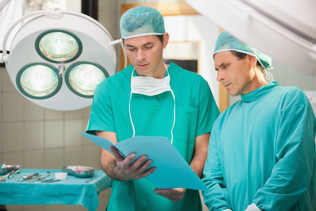 Two surgeons looking at medical records