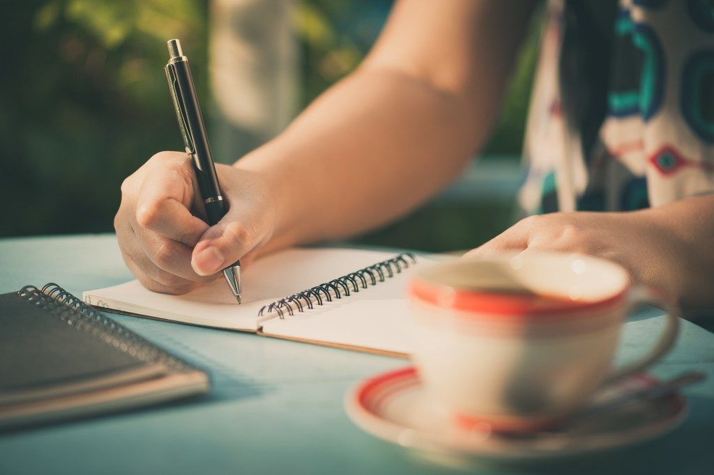 person writing on a journal
