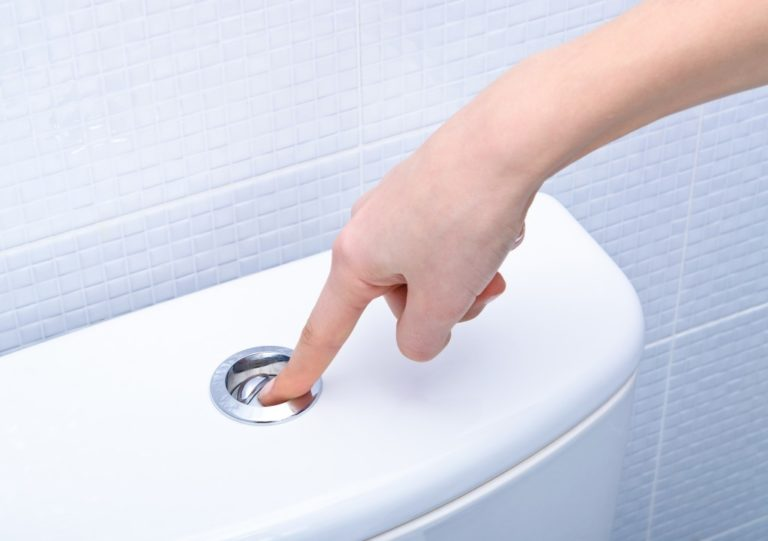 person pushing the flush button of a toilet
