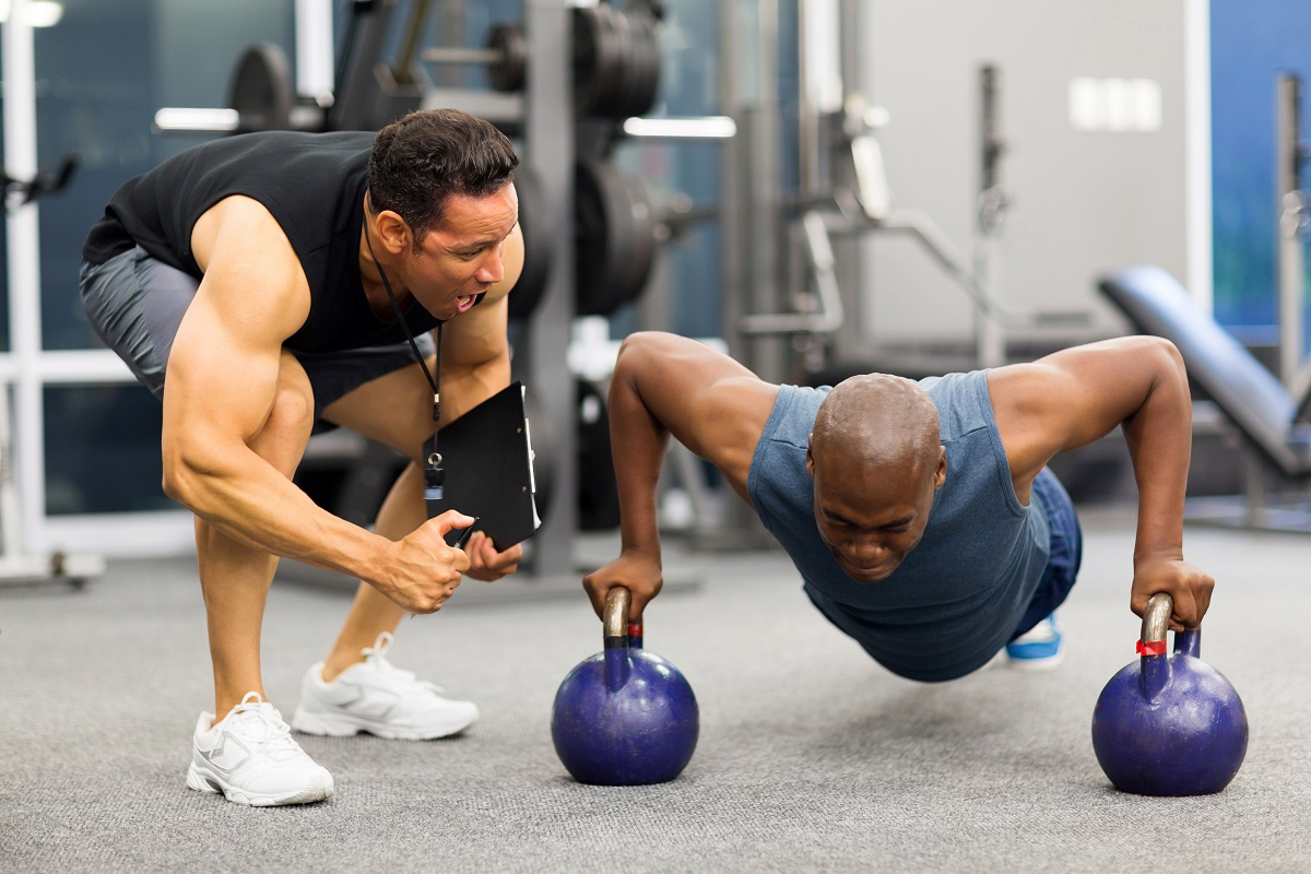 Man doing kettlebell pushups with trainer