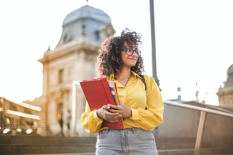young woman holding books and binder in campus