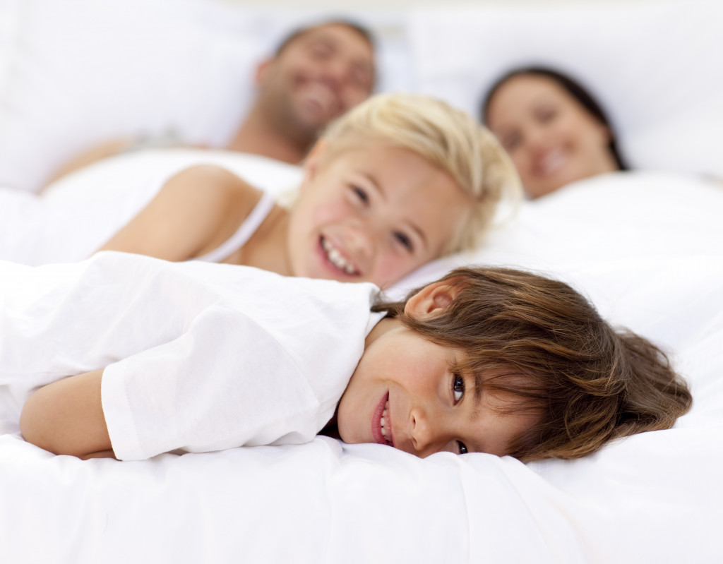 family relaxing on a bed