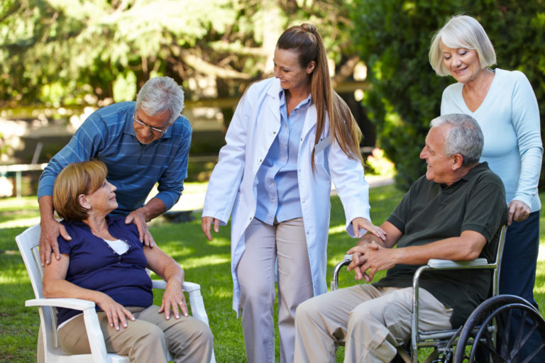 2 elderly people on wheelchair smiling with a doctor along with another 2 elderly people