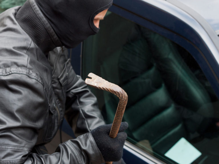thief opening a car with a crowbar