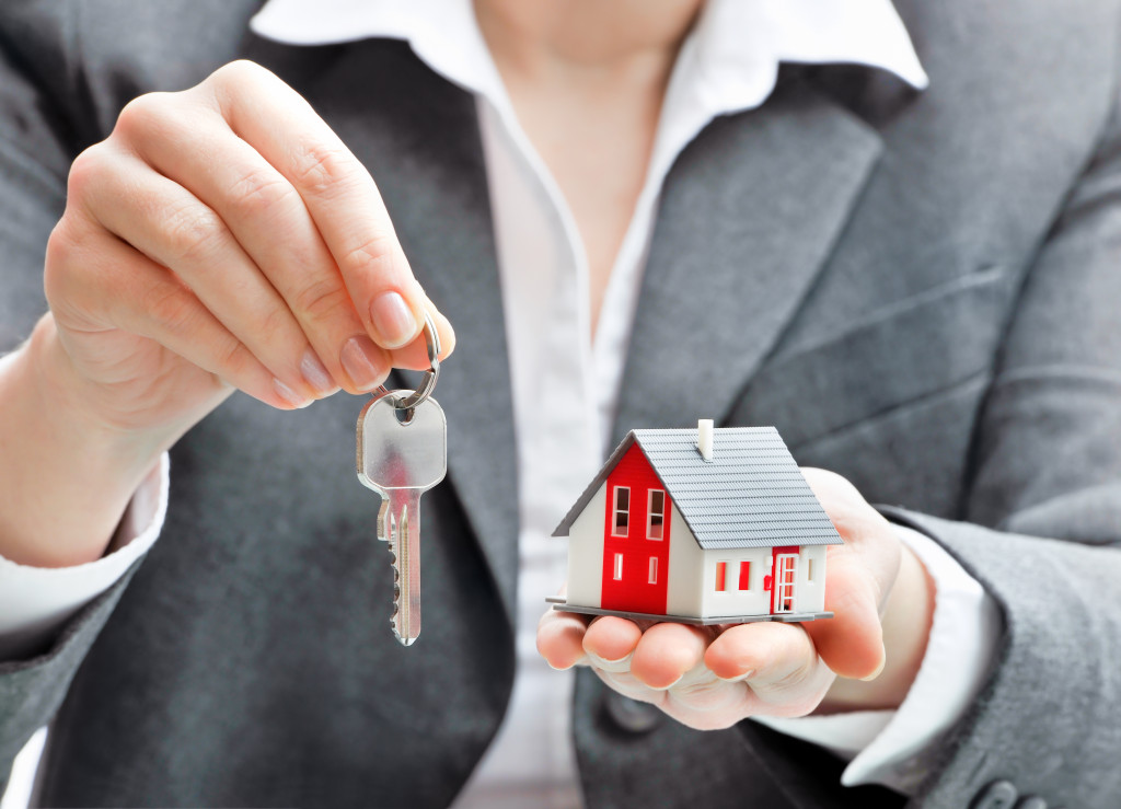 a person holding a key and a cardboard replica of a house