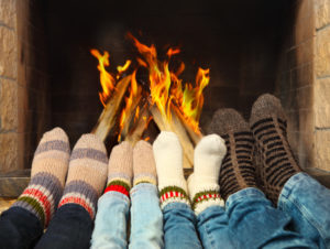 four sets of feet in front of a fireplace