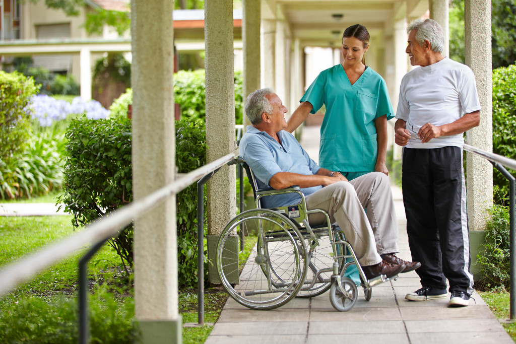 elderly man on wheelchair smiling with a nurse and another elderly man