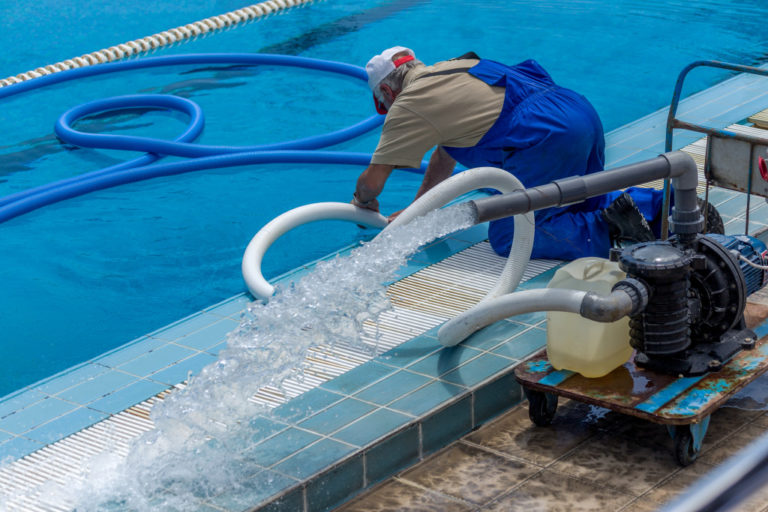 person cleaning the pool
